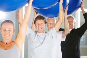 Mann in Gruppe bei Fitnesstraining mit Gymnastikball