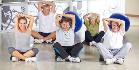 Gruppe Senioren beim Dehnen im Fitnesscenter