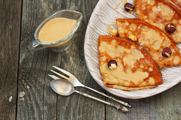 pancakes on a plate with caramel sauce and nuts on a wooden back