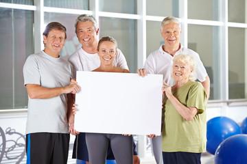 Gruppe Senioren hält Plakat im Fitnesscenter
