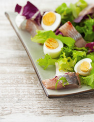 salad with herring, fresh herbs and quail eggs on a  wooden back
