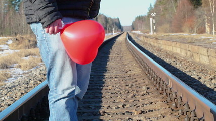 Man with red heart-shaped balloon on the railway