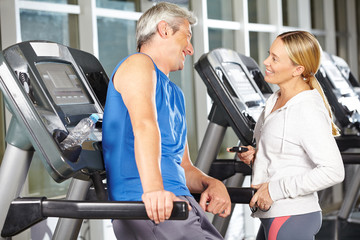 Zwei Senioren reden im Fitnesscenter miteinander