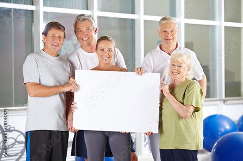 Gruppe Senioren hält Plakat im Fitnesscenter - 78334827