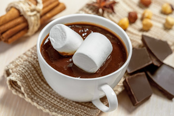 Hot chocolate with marshmallows, cinnamon and nuts on table
