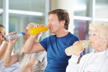 Gruppe Senioren beim Trinken im Fitnesscenter