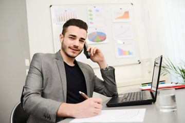 young man in office working with laptop computer and phone