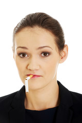 Businesswoman with broke cigarette in mouth.