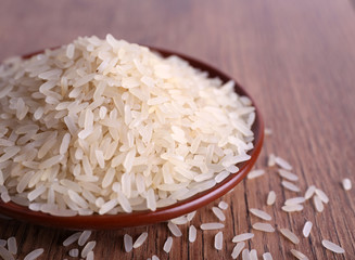 Grain of rice on plate on wooden background