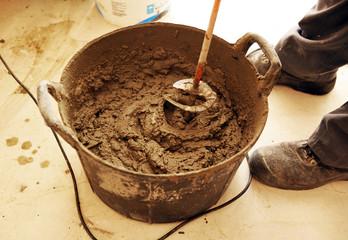 Albañil haciendo mezcla de cemento con batidora