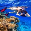 Young women snorkeling in the tropical water with camera - 78337459