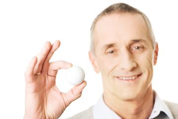 Mature man holding golf ball