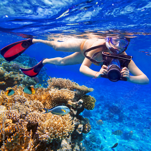 Fotobehang Duiken Young women snorkeling in the tropical water with camera