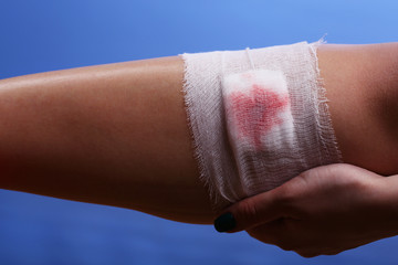 Wounded leg with bandage on blue background