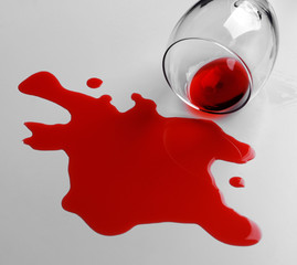 Red wine spilled from glass on white background