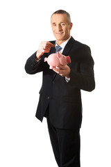 Cheerful businessman holding piggybank