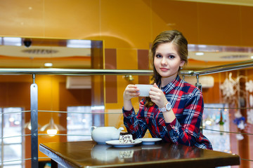 Young nice girl in a plaid shirt drinking tea in a cafe