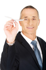 Portrait of businessman throwing a paper plane