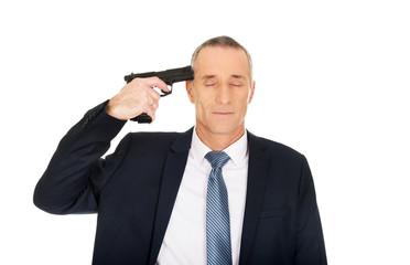 Portrait of a man with handgun near head
