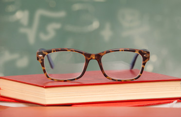 Glasses laying on a staple of Books
