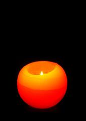 Orange Sphere candle isolated on black