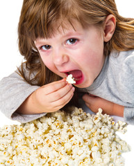 pretty young girl eating a pop corn on bowl
