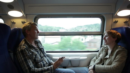 man and woman go by  train sitting  friend opposite to  friend a