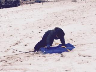 niño con su trineo jugando en la nieve
