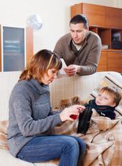 Parents giving liquid medicament to unwell  son