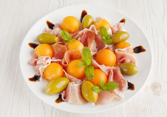 Melon and prosciutto ham salad & green olives. light lunch. heal
