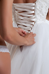 Sexy girl laces corset of bridal gown