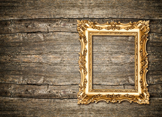 Baroque golden frame over wooden background. Grungy texture
