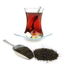 Turkish tea  in traditional glass and dry black tea leaves .