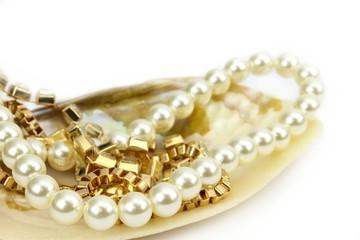 Perlenkette und Goldschmuck in Muschel