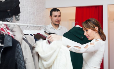 Smiling adult couple choosing clothes