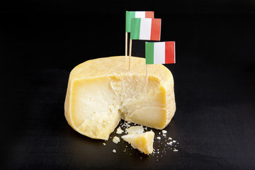whole of parmesan with handle cheese knife & italian flag. on bl