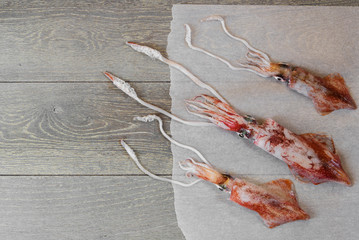 Fresh squids on wooden table