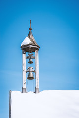 Snow covered alpine chapel tower
