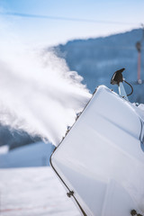 Snowmaker spraying water on a ski slope