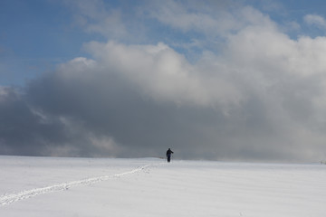 Man on ski track against cloudy sky