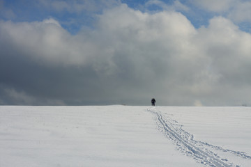 Man and woman on ski track against cloudy sky