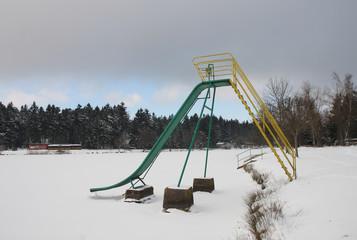 abandoned slide on frozen lake in winter