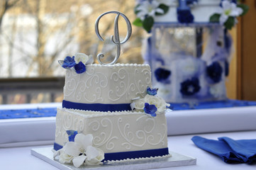 White Wedding Cake with Blue Flowers and P Monogram