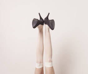 Female legs up in the air wearing heels and posing