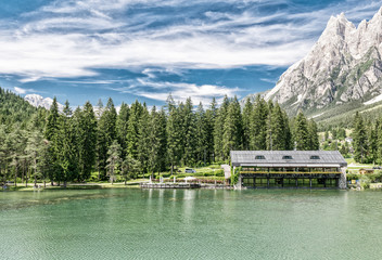 Beautiful hut over the lake in the middle of mountains valley