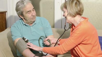 Nurse Checks Senior Blood Pressure