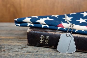 military dog tags on flag and Bible