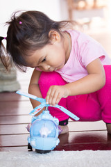 Cute little girl is playing toy