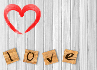 heart on white wooden background. Love cast out of wooden bricks