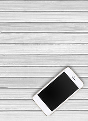 Modern mobile phone on white wooden background